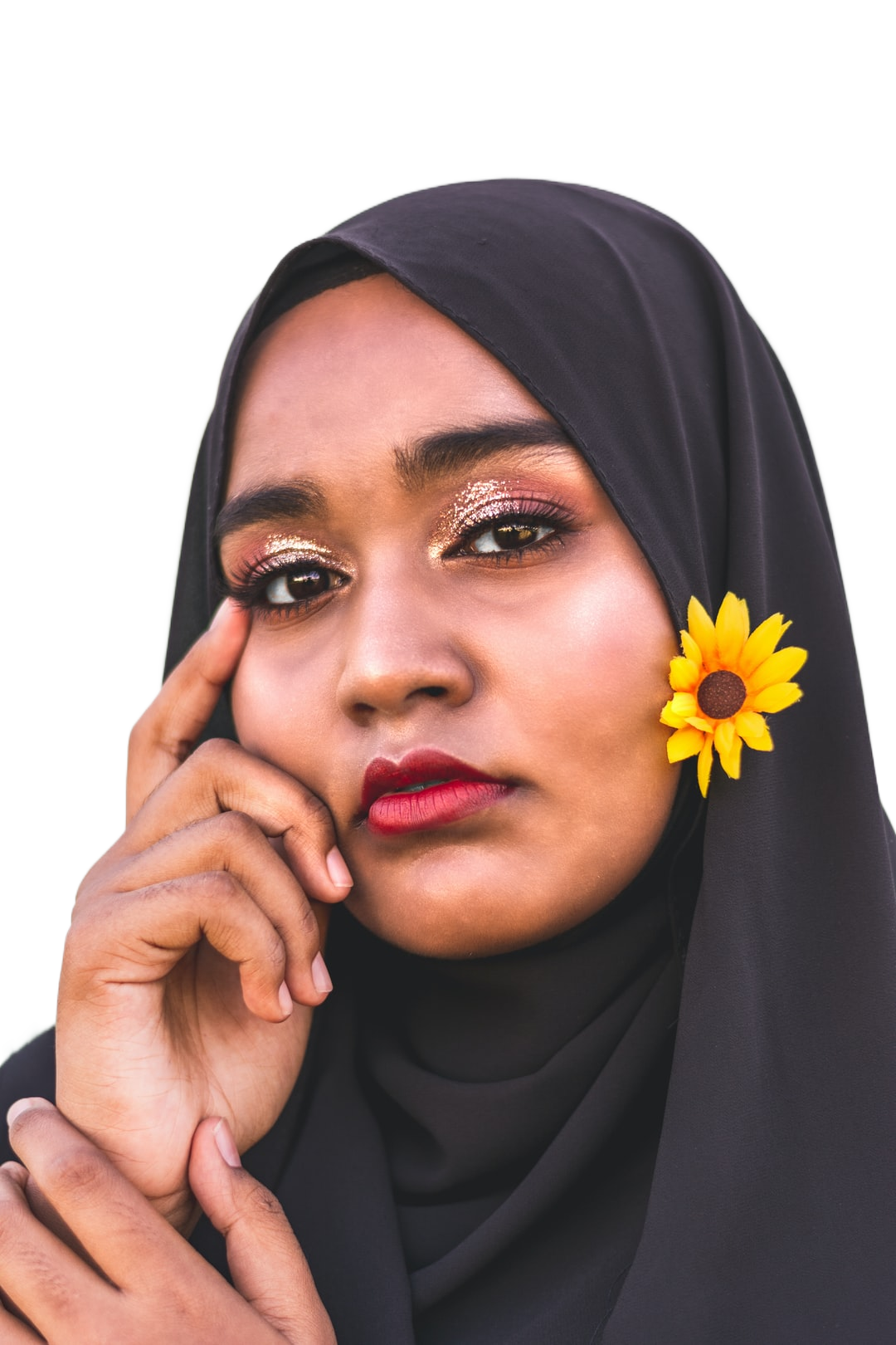 woman in black hijab holding sunflower
