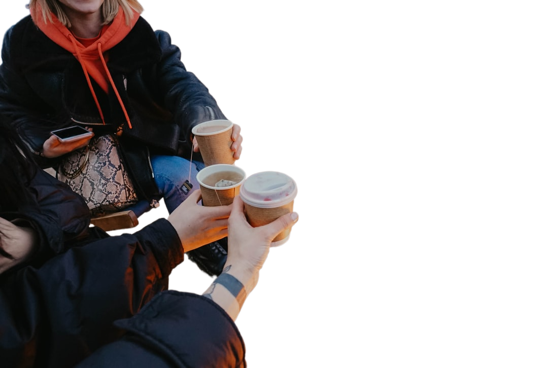 person in black jacket holding white disposable cup