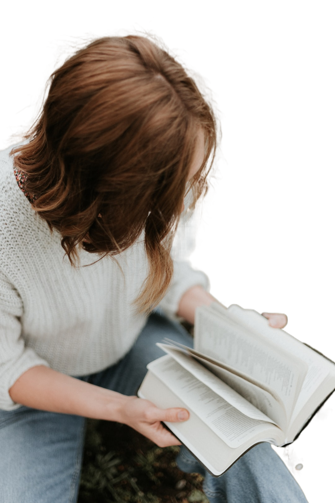 woman sitting on concrete floor reading book