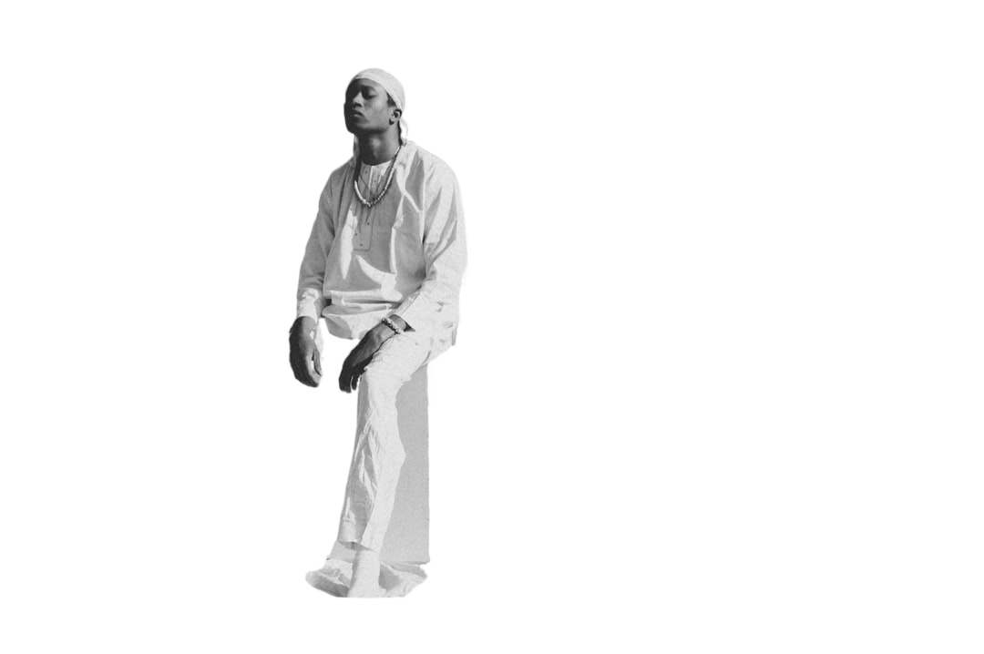 man in white dress shirt and black pants standing on white textile